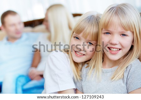 Portrait of happy twin girls looking at camera with their parents behind