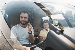 Portrait of happy unshaven pilot and smiling child sitting in cabin of contemporary helicopter. They wearing headsets. Glad male talking in microphone