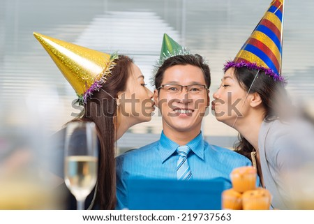 Portrait of happy Vietnamese birthday man being kissed by two his colleagues