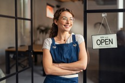 Portrait of happy waitress standing at restaurant entrance. Portrait of young business woman attend new customers in her coffee shop. Smiling small business owner showing open sign in her shop.