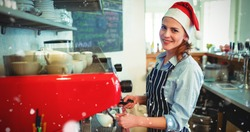 Portrait of happy waitress wearing Santa hat against snow falling