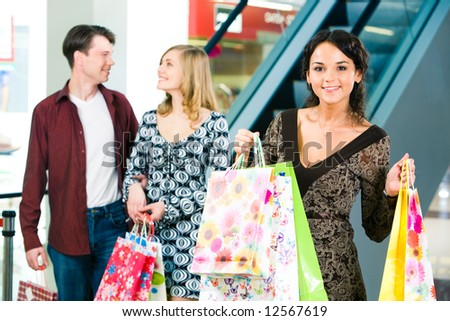 Portrait of happy woman carrying bags and looking at camera on the background of young couple
