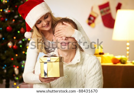 Portrait of happy woman closing male?s eyes by her hands while holding giftbox in front of him