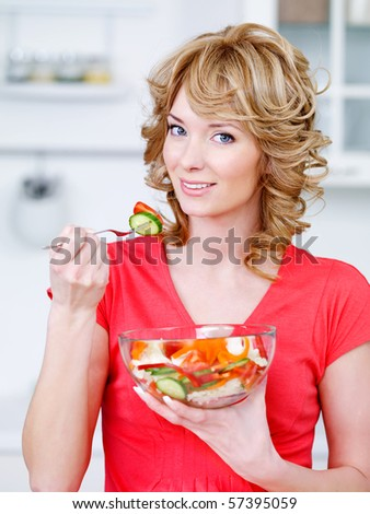 Portrait of happy woman eating the salad of vegetables in the kitchen