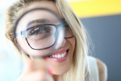 Portrait of happy woman having fun and looking through magnifying glass. Blonde attractive lady wearing trendy black glasses. Cheerful person. Joy and happiness concept