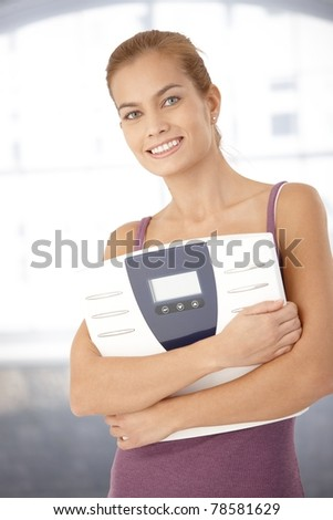 Portrait of happy woman holding scale in arms, smiling at camera.?