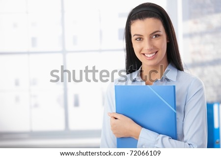 Portrait of happy woman in office, standing with folder, smiling at camera.?