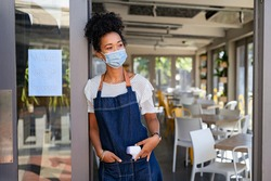 Portrait of happy woman standing at doorway of her cafeteria while wearing protective face mask during coronavirus pandemic. Hopeful black waitress waiting for clients at coffee shop with thermometer.