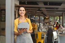Portrait of happy woman standing at doorway of her store. Cheerful mature waitress waiting for clients at coffee shop. Successful small business owner in casual wearing grey apron standing at entrance