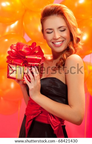 portrait of happy woman trying to guess what is in the gift box over pink background - stock photo