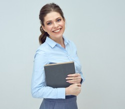 portrait of happy woman wearing blue shirt holding book.