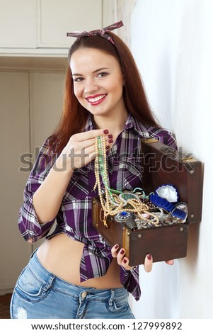 portrait of happy woman with jewelry in treasure chest in home