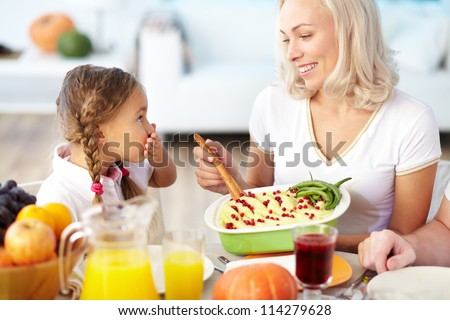 Portrait of happy woman with mashed potatoes and her daughter sitting at festive table - stock photo