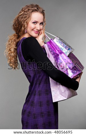 portrait of happy woman with purchases against grey background