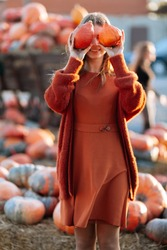 Portrait of happy woman with ripe orange pumpkins in hands close eyes near wagon with orange pumpkin on farmers market in brown sweater, dress. Cozy autumn vibes Halloween, Thanksgiving day