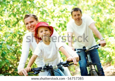 Portrait of happy woman with son riding a bicycle in park on background of male