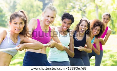 Portrait of happy women pulling a rope in tug of war at the park