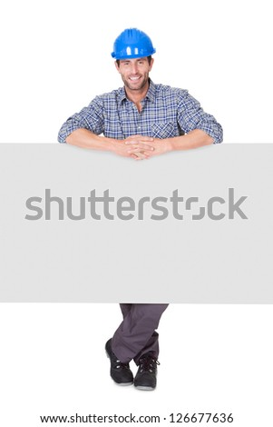 Portrait of happy worker presenting empty banner. Isolated on white