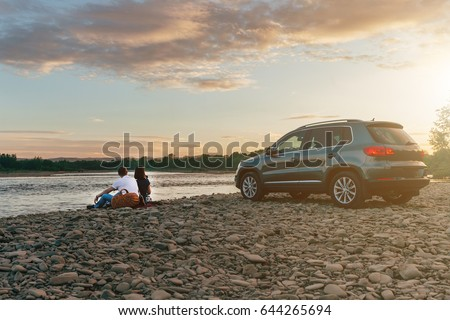 Portrait of happy young adult couple with dog on roadtrip. Man sitting on plaid with woman and watching sunset near river. Outdoor picnic concept.