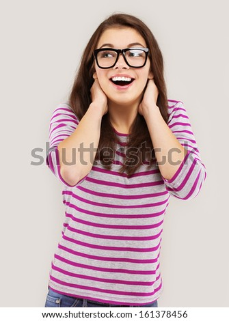 Portrait of happy young adult woman wearing glasses, looking up and laughing - stock photo
