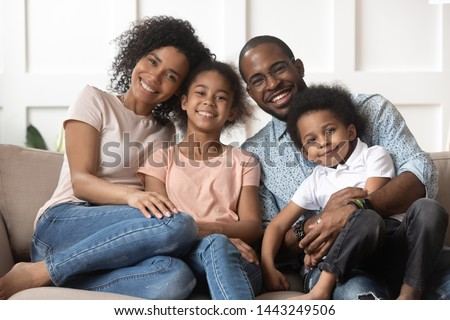 Portrait of happy young african American family with little kids sit relax on couch cuddling, smiling black parents rest on sofa hug preschooler children posing for picture at home together