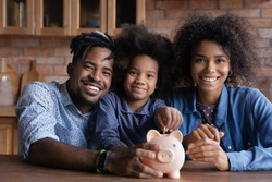 Portrait of happy young African American family with teen daughter put coin save money in piggybank. Smiling economical ethnic parents with child feel provident make financial investment for future.