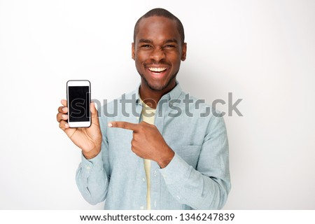 Portrait of happy young african american man holding mobile phone and pointing to screen #1346247839
