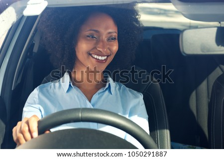 Portrait of happy young african american woman driving a car and smiling #1050291887