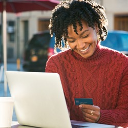 Portrait of happy young african woman holding a credit card and shopping on internet. Girl using laptop for online banking at cafe. Smiling woman using laptop and credit card for online payment.