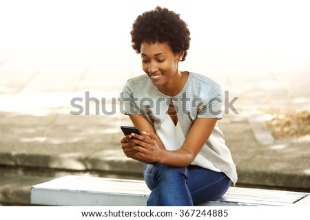 Portrait of happy young african woman sitting outside on bench reading a text message on her mobile phone