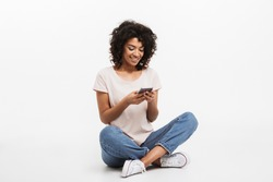 Portrait of happy young afro american woman using mobile phone while sitting on a floor with legs crossed isolated over white background