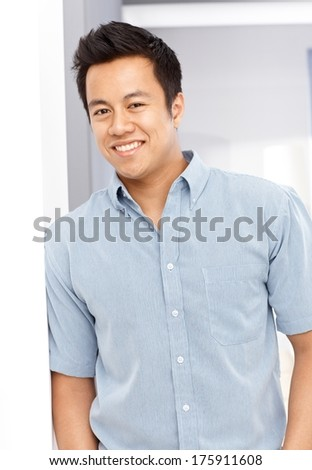 Portrait of happy young Asian man leaning against wall, looking at camera.