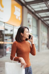 Portrait of happy young Asian woman talking on mobile and carrying paper shopping bags walking outdoor mall