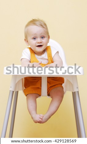 Portrait Of Happy Young Baby Adorable Boy In High Chair. laughing and waiting for food Stock foto ©
