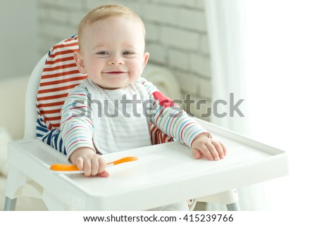 Portrait Of Happy Young Baby Boy In High Chair  #415239766