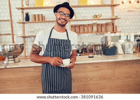 Portrait of happy young barista at work. Caucasian man wearing apron and hat standing in front of cafe counter with cup of coffee and looking at camera smiling.