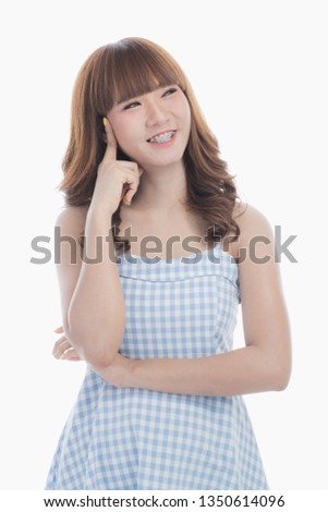 Portrait of happy young beautiful Asian woman with brace retainers with dark brown hair in light blue checked dress standing with arms crossed body and touch her temple on isolated white background