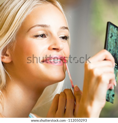 Portrait of happy young beautiful woman applying lipstick at home