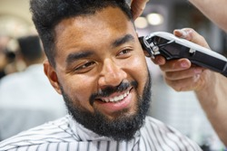 Portrait of happy young black man being trimmed with professional electric clipper machine in barbershop.Male beauty treatment concept.Smiling young African guy getting new haircut in barber salon