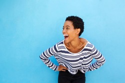 Portrait of happy young black woman laughing against blue background