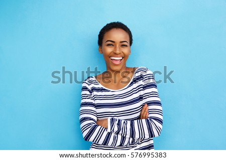 Portrait of happy young black woman laughing against blue wall #576995383
