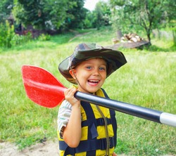 Portrait of happy young boy holding paddle near a kayak on the river, enjoying a lovely summer day