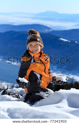 Portrait of happy young boy playing with snow on Alpine mountain summit. - stock photo