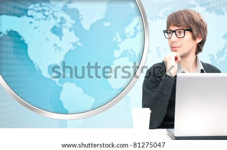 Portrait of happy young business man using his laptop. World map on the background