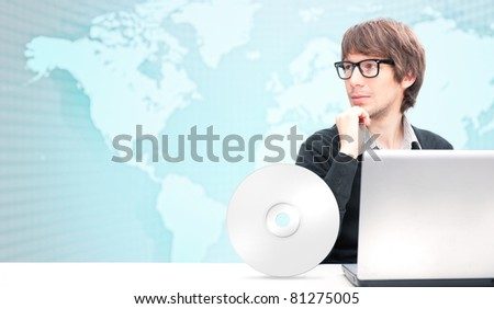 Portrait of happy young business man working using laptop against world map.