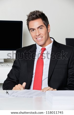 Portrait of happy young businessman sitting at desk in office