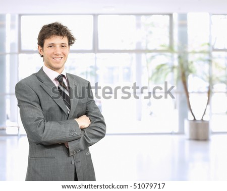 Portrait of happy young businessman standing in confident pose with arms crossed in office lobby, smiling.