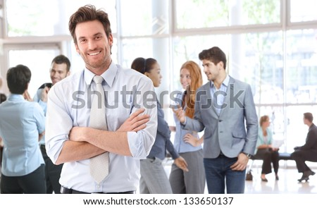 Portrait of happy young businessman standing in office lobby, people talking in background.