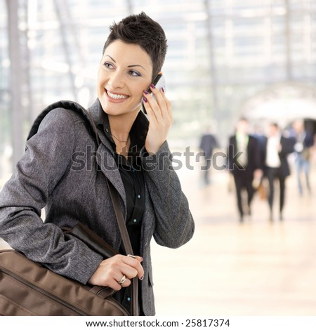 Portrait of happy young businesswoman calling on mobile phone, smiling.
