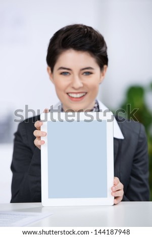 Portrait of happy young businesswoman displaying digital tablet at counter
